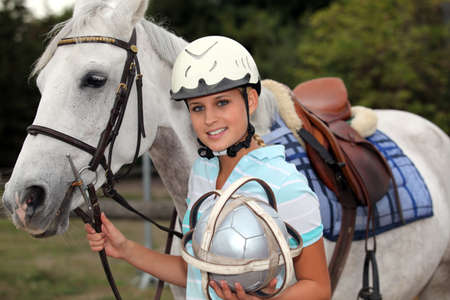 professional female jockey posing with her horse photo