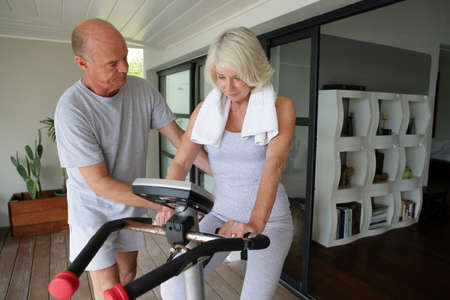 Man helping his wife use an exercise machine photo
