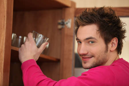 Man getting a glass out of the cupboard Stock Photo - 12636899