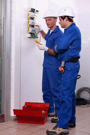 Two electricians checking power supply photo