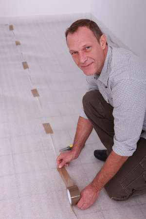 A man laying a new floor  Stock Photo - 12637993