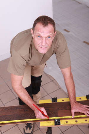 Man at home cutting wooden flooring to size photo