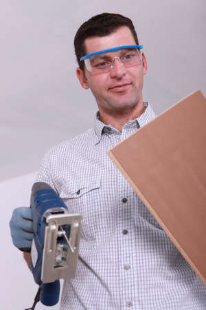 tongue and groove: Worker with a jigsaw and a plank of wood Stock Photo