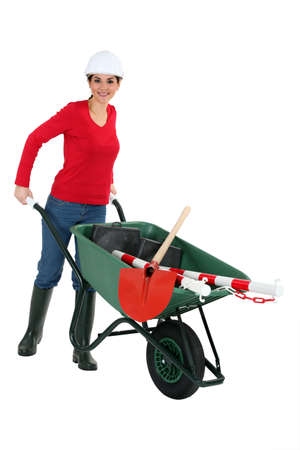 craftswoman: craftswoman transporting instruments with a wheelbarrow