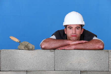 bricklayer with trowel head resting on arms photo