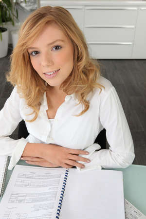 coursework: Student looking at her coursework Stock Photo