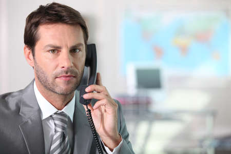 Businessman on the telephone with serious expression on face photo