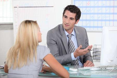 Hombre de traje hablando con una mujer joven en un escritorio Foto de archivo