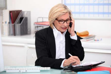 economia aziendale: Donna al telefono nel suo ufficio Archivio Fotografico