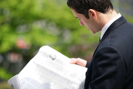 financial newspaper: Businessman reading newspaper in park Stock Photo