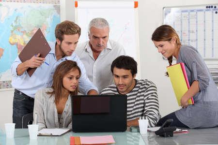 profesor: Los estudiantes y maestros se reunieron alrededor de ordenador portátil