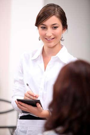 prestar atencion: Una mujer de negocios tomando notas Foto de archivo