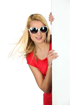 Studio shot of a young woman in sunglasses with a board left blank for your image photo
