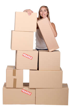 stockroom: Young woman with a pile of cardboard boxes marked fragile Stock Photo