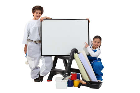housepainter: two children dressed in housepainter and a whiteboard Stock Photo