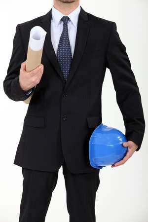 Architect carrying his helmet and a blueprint Stock Photo - 12600295