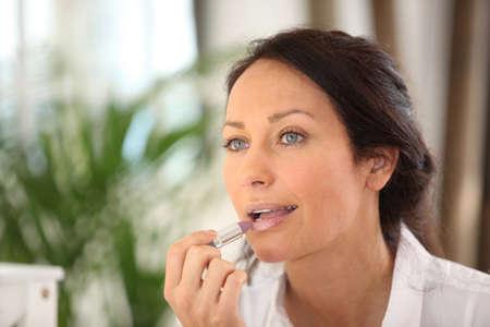 suitor: brunette putting on mauve lipstick