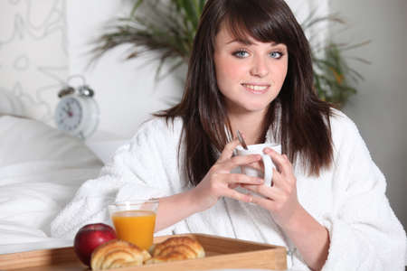 Teenage girl having breakfast in bed photo