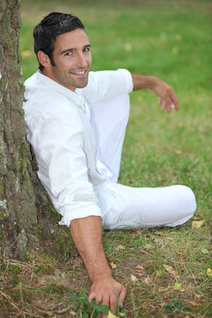 dressed up: Man relaxing under a tree