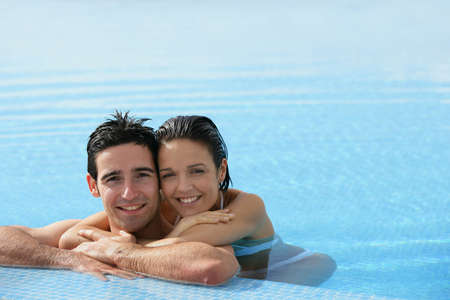 Affectionate couple in swimming pool photo