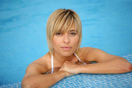 Blond woman resting by the edge of the swimming pool photo