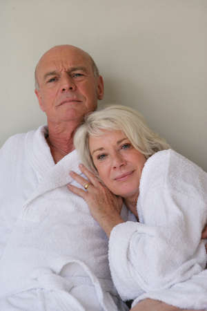 Retired couple sat in bathing robes photo