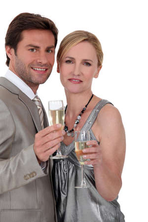Couple drinking champagne in cocktail dress photo