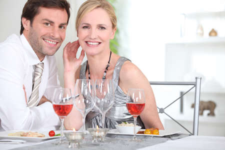 An elegant couple having dinner and smiling at us  Stock Photo