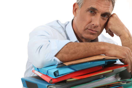 50 55: Man leaning on stack of work Stock Photo