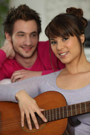 Girlfriend playing the guitar for her boyfriend photo