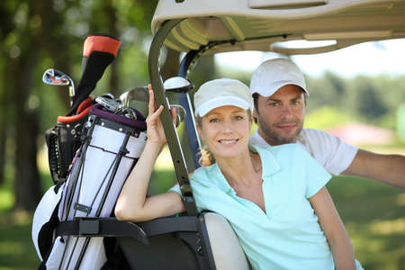 woman golf: Couple in golf cart