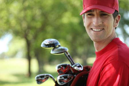 golf landscape: Golfer holding golf clubs smiling