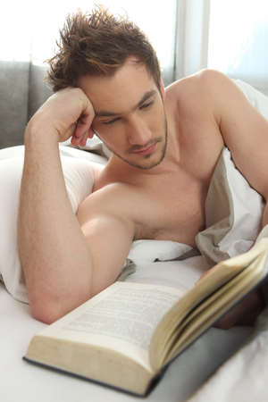 bare chested: Man reading in bed