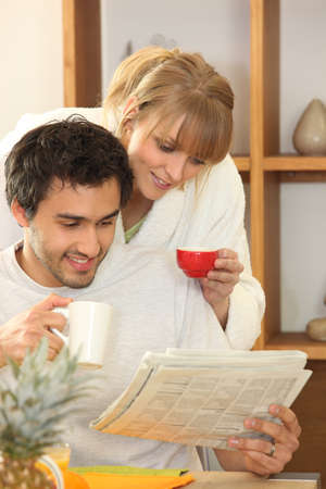 Couple drinking coffee and looking at a newspaper together photo