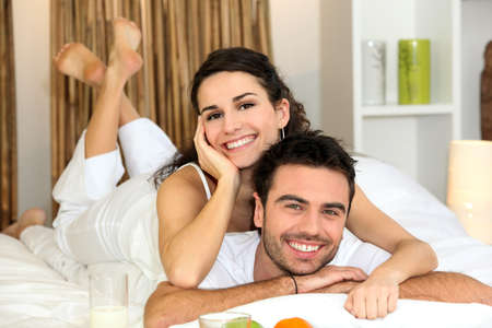 40s: Couple laying in bed together Stock Photo