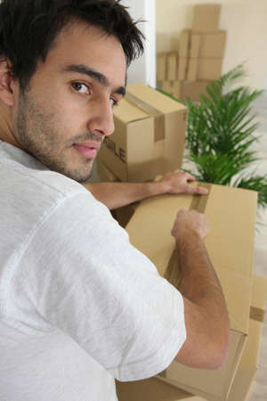 Young man packing boxes photo