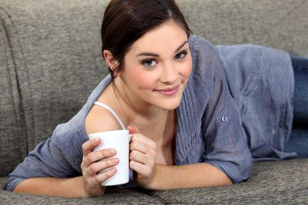 calm down: Woman laying on sofa with mug of coffee Stock Photo