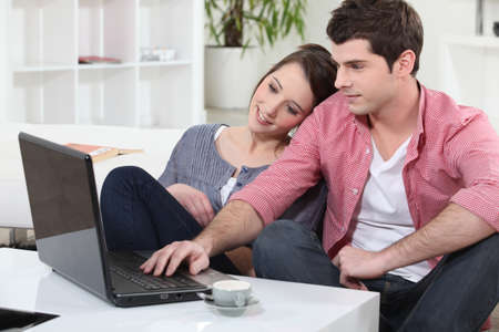 Couple relaxing at home in front of their laptop photo