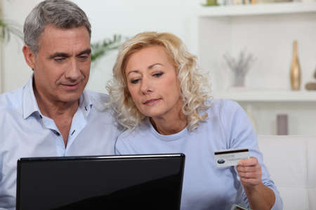 Older couple using a credit card online photo
