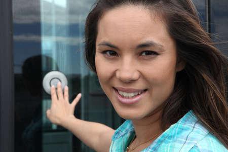 Closeup young woman pressing bell