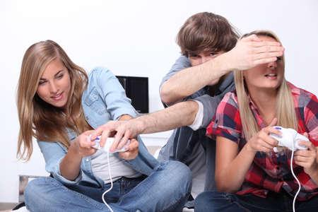 jugando videojuegos: Tres adolescentes sentados jugando juegos de video