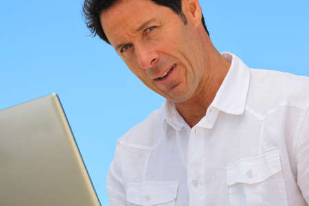 40 45: Man on laptop in blue sky Stock Photo