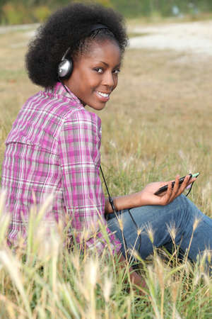 aridness: Woman listening to music in a field Stock Photo