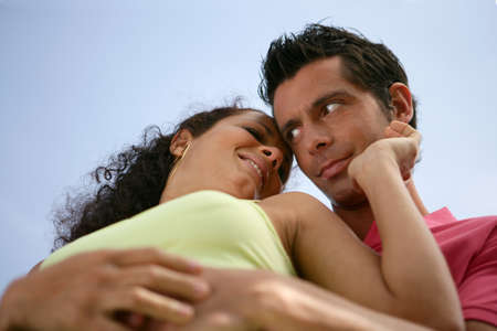 Low-angle view of couple stood hugging outdoors photo