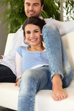 Smiling man and woman on phone on a sofa photo