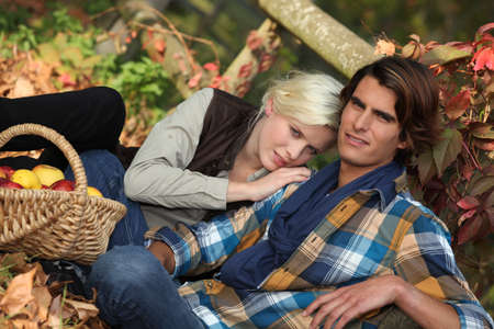 man nuts: couple sitting in dead leaves Stock Photo