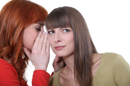 Woman whispering into her friend photo