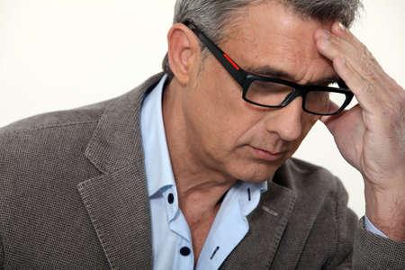 senior depression: Stressed businessman wearing glasses
