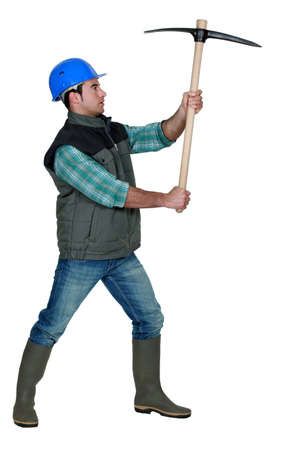 mattock: picture of craftsman holding pickaxe in profile