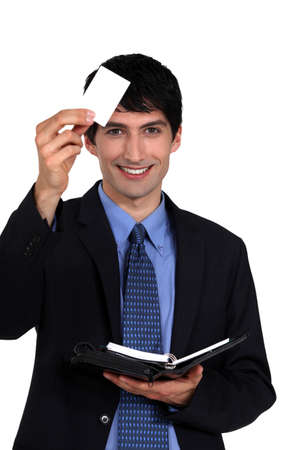 Executive with a blank businesscard and diary photo